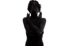 A Young female fashion model. Painted black with body paint in studio Royalty Free Stock Photo