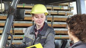 Young female fatory worker operating forklift at the storage talking to her colleague stock photos