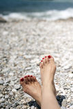Young female feet on the beach with blue water Stock Photography