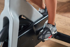 Young female feet exercising and pedaling a stationary bicycle Royalty Free Stock Photos