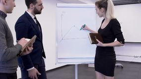 Young female financial analytic is presenting the bitcoin maret changes for her colleagues in boardroom. Businessman in blue suit and male intern in grey stock video
