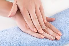 Young female fingers with orange manicure. Young woman fingers with orange manicure on nails holding hand on blue towel in beauty studio. Close up, selective stock image
