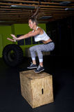 Young Female Fitness Instructor Trainer. Young female fitness trainer jumps up onto wooden box Royalty Free Stock Photos