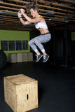 Young Female Fitness Instructor Trainer. Young female fitness trainer jumps up onto wooden box Stock Photo