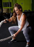 Young Female Fitness Instructor Trainer. Young female fitness trainer works out with heavy ropes Royalty Free Stock Images