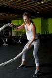 Young Female Fitness Instructor Trainer. Young female fitness trainer works out with heavy ropes Stock Image