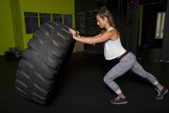 Young Female Fitness Instructor Trainer. Young female fitness trainer works out with a heavy tractor tire Stock Photography