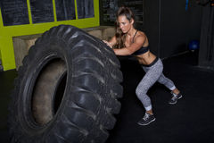 Young Female Fitness Instructor Trainer. Young female fitness trainer works out with a heavy tractor tire Stock Images