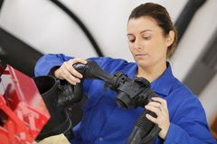 Young female fixing mechanical part in workshop Royalty Free Stock Image