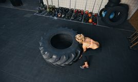 Young female flipping heavy tire. Top view of young female flipping heavy tire. Woman doing crossfit workout at gym royalty free stock photos