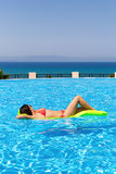 Young female floats in infinity pool royalty free stock images