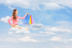 Young female flying on cloud and holding bags against cloudy sky Royalty Free Stock Photo