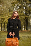 Young female in forest. With handbag looking away Royalty Free Stock Photography