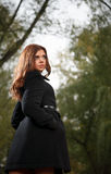 Young female in forest. Young female wearing black coat in forest looking away Royalty Free Stock Photography