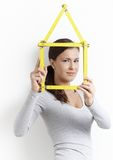 Young female forming house from folding rule Royalty Free Stock Photo