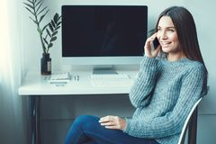 Young woman freelancer indoors home office concept casual style phone communication. Young female freelancer at home office casual sitting talking by phone Stock Photo