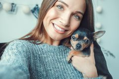 Young woman freelancer indoors home office concept casual style photos with dog. Young female freelancer at home office casual taking seelfie pictures with dog royalty free stock photography