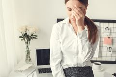 Young woman freelancer indoors home office concept formal style tired. Young female freelancer at home office formal feeling unwell tired stock image
