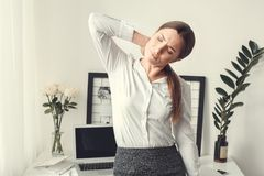Young woman freelancer indoors home office concept formal style muscle pain. Young female freelancer at home office formal neck muscle pain tired stock photography