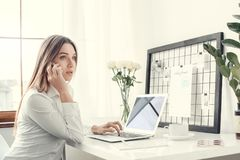 Young woman freelancer indoors home office concept formal style smartphone communication. Young female freelancer at home office formal sitting answering phone Royalty Free Stock Photos