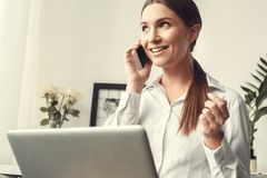 Young woman freelancer indoors home office concept formal style sitting smartphone communication close-up. Young female freelancer at home office formal sitting Stock Photos