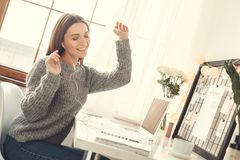 Young woman freelancer indoors home office concept winter atmosphere sitting listening music. Young female freelancer at home office winter sitting listening to stock photo