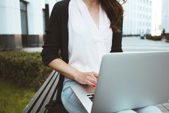Young female freelancer making labor market research on modern laptop, sits on outdoors in urban street royalty free stock images