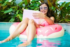 Young female freelancer sitting with a laptop in an inflatable circle in the pool. Busy during the holidays. Remote work royalty free stock photography