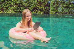 Young female freelancer sitting near the pool with her laptop in the hotel browsing in her smartphone. Busy at holidays. Distant work concept. Copy space for royalty free stock images
