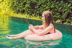 Young female freelancer sitting with a tablet in an inflatable circle in the pool. Busy at holidays. Distant work. Concept. Copy space for your text royalty free stock photos