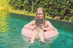 Young female freelancer sitting with a tablet in an inflatable circle in the pool. Busy at holidays. Distant work. Concept. Copy space for your text stock photos