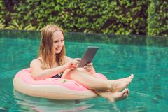 Young female freelancer sitting with a tablet in an inflatable circle in the pool. Busy at holidays. Distant work. Concept. Copy space for your text stock photo
