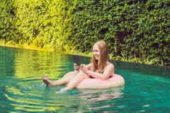 Young female freelancer with a tablet in the inflatable circle in the pool. Busy at holidays. Distant work concept. Copy. Space for your text stock image