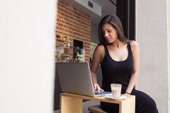 Young female freelancer working on her laptop computer while sitting in modern coffee shop during lunch break in summer day. Gorgeous latin woman connecting to Stock Photo