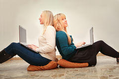 Young female friends addicted to internet use laptops Stock Images