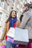 Young female friends carrying shopping bags outdoors Royalty Free Stock Image