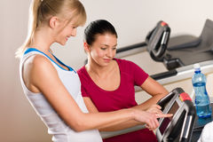 Young female friends chatting in fitness center Stock Photo