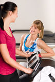Young female friends chatting in fitness center Royalty Free Stock Photo