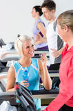 Young female friends chatting in fitness center Stock Images