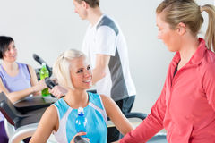 Young female friends chatting in fitness center Stock Photos