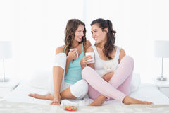 Young female friends with coffee cups in bed. Full length of cheerful young female friends with coffee cups in bed at home stock photos