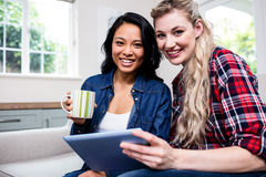 Young female friends with cup and digital tablet on sofa Royalty Free Stock Photo