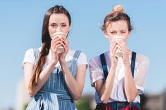 young female friends drinking coffee from paper cups stock image