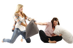 Young female friends enjoying pillow fights Stock Photos