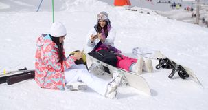 Young female friends relaxing with snowboards. Two attractive young female friends relaxing with their snowboards sitting in the snow in their ski clothes and stock video footage