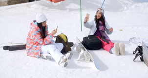 Young female friends relaxing with snowboards Stock Photo