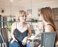 Young female friends spending leisure time at restaurant Stock Photos