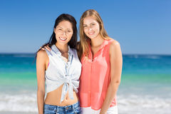 Young female friends standing on beach Royalty Free Stock Photo