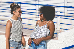 Young female friends standing outside talking Royalty Free Stock Images