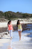 Young Female Friends Strolling at the Beach Stock Photography